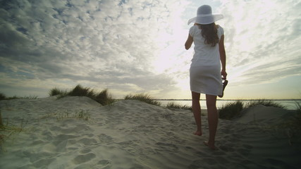 Young woman walking on a beach sand dune in slow motion