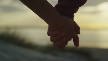 Unseen couple holding hands at the beach at sunset