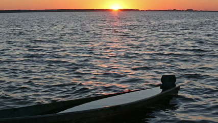 Sunset and drowned boat on summer lake bank.