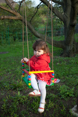 Capricious little girl on a swing