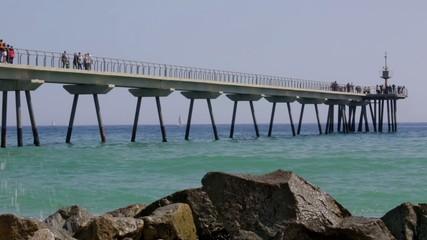 Footbridge over the sea with people walking