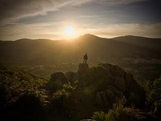 Hombr en lo alto de la cima contempla la puesta de sol