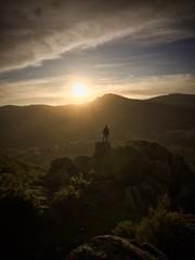 Hombre en lo alto de la montaña contempla la puesta de sol 2