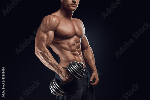 Poster, Tablou Strong and power bodybuilder doing exercises with dumbbell