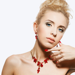 Portrait of beautiful blond woman with a ruby jewelry on. Natura