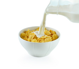 tasty cornflakes in white  bowl and glass of milk on white backg