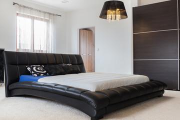 Huge leather bed in bedroom
