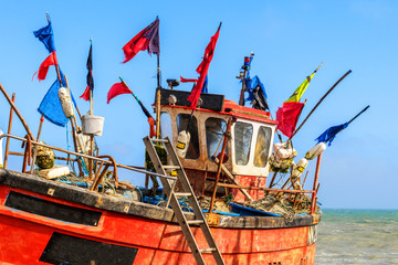 Bright pot flags flying on a small, beach launched fishing boat