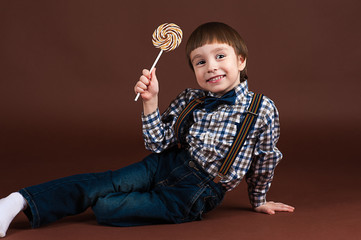 smiling boy sitting on the floor with a lollipop
