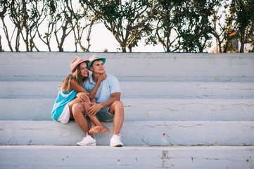 Happy young couple sitting on stairs smiling love resting