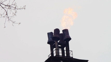 Plant. Pipes factory on sky background from which the fire