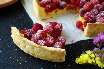 Piece of sweet pie with raspberries on slate