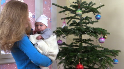 woman kiss cute baby and sway in hands near Christmas tree