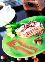 Slice of cake on plate with hazelnuts.