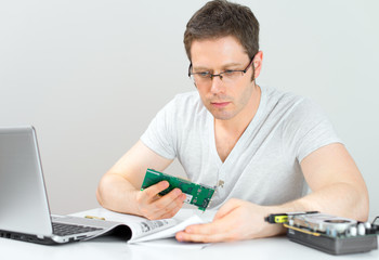 Male technician reading manual at his workplace.