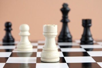 Chess pieces on a chessboard on a beige background.