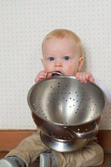Baby boy is playing with a pasta strainer.