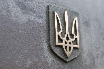 Coat of arms of Ukraine on wall.