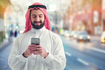 Arab businessman working with his phone on a crowded street