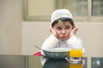 Arabian kid having breakfast of cornflakes & orange juice