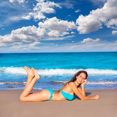 Brunette tourist lying in beach sand tanning happy