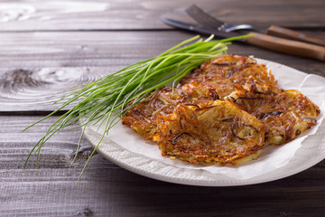 Potato fritters, green onions on a wooden surface