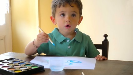 portrait of little boy painting with watercolors