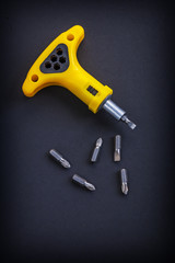 yellow screwdriver with little bits on black background
