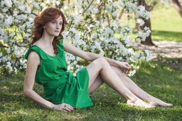Model woman with Apple blossoms in a spring garden