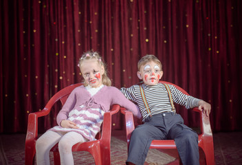 Boy and Girl Dressed as Clowns Sitting on Chairs