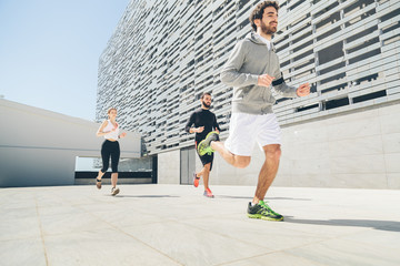 Three young friends running in front of a building