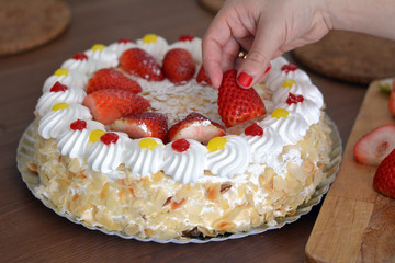 Woman hand is decorating a cream cake with strawberries