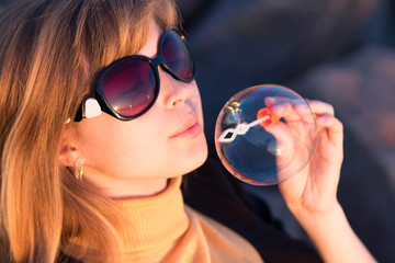 Young girl in sunglasses blowing soap bubbles