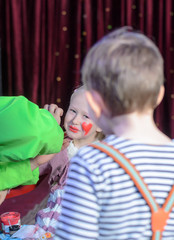 Boy Watching Girl Have Face Painted