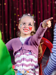 Girl Dressed as Clown Smiling and Pointing