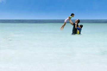 Man throwing her daughter on beach