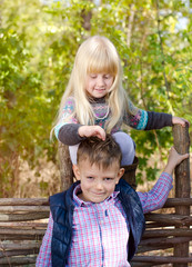 Cute Blond Girl Playing the Hair of her Brother