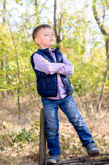 Boy Standing with Arms Crossed in Forest