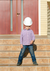 Boy Wearing Hard Hat Standing on Stairs