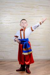 Little boy in colorful costume doing folk dancing