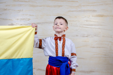 Cute child holding the national flag of Ukraine