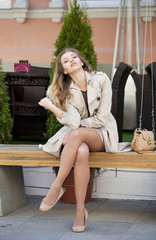 Young beautiful girl in a beige coat sitting on a bench in the s