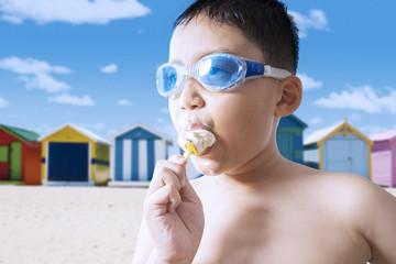 Naked child eating ice cream at coast
