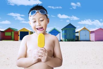 Naked male kid eating ice cream at coast