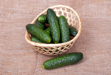 Cucumbers in a wicker basket on burlap, top view