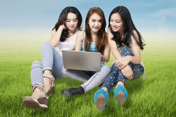 Three students with laptop in nature