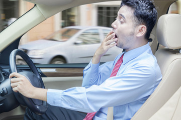 Tired man driving a car