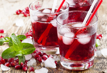 Fresh red juice cocktail with pomegranate seeds, mint and ice, s