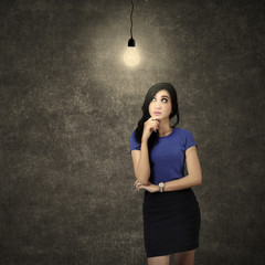 Woman thinking under light bulb
