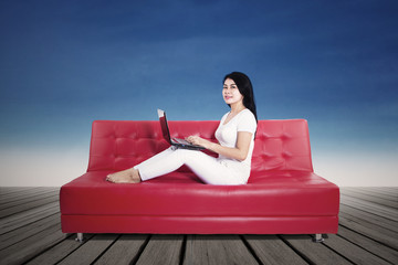 Woman using laptop on sofa outdoors